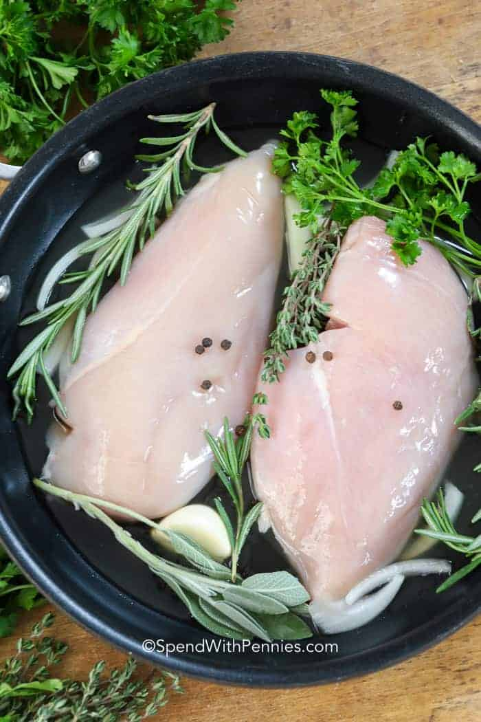 Raw chicken breasts in a pan with fresh herbs ready to be poached