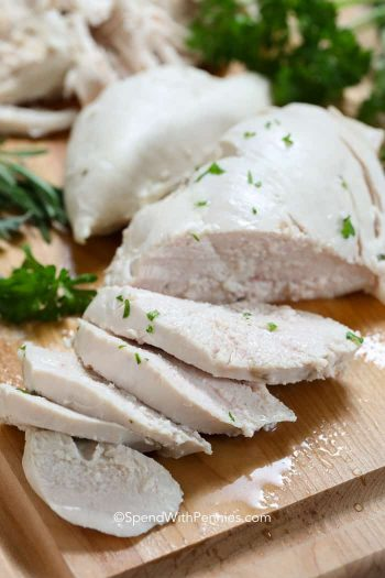 Slices of poached chicken on a wooden board