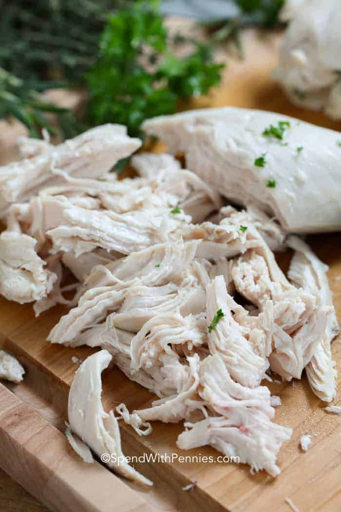 Shredded poached chicken breasts on a cutting board