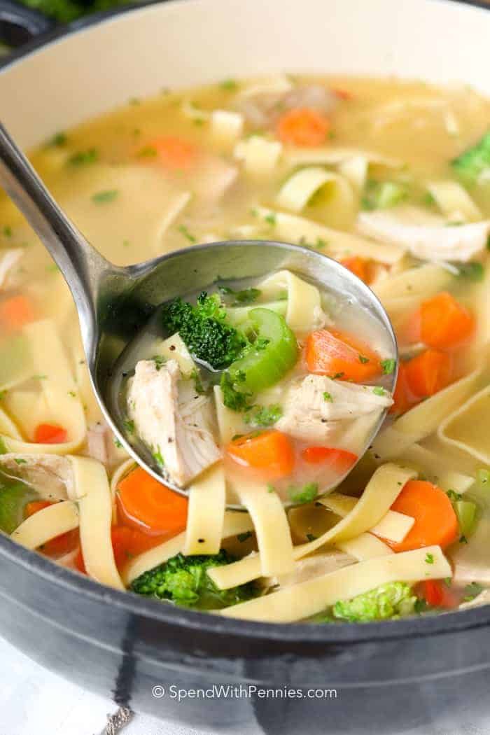 A ladle of homemade chicken noodle soup
