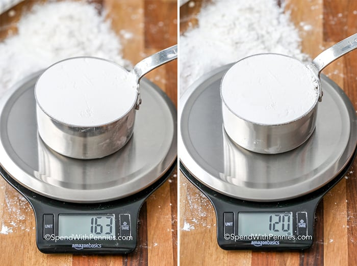 Two shots of flour in measuring cups being weighed on a kitchen scale