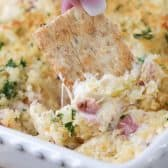 Reuben Dip being dipped with a cracker