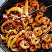 Skillet Shrimp Fajitas, peppers and onions in a cast iron pan with tongs