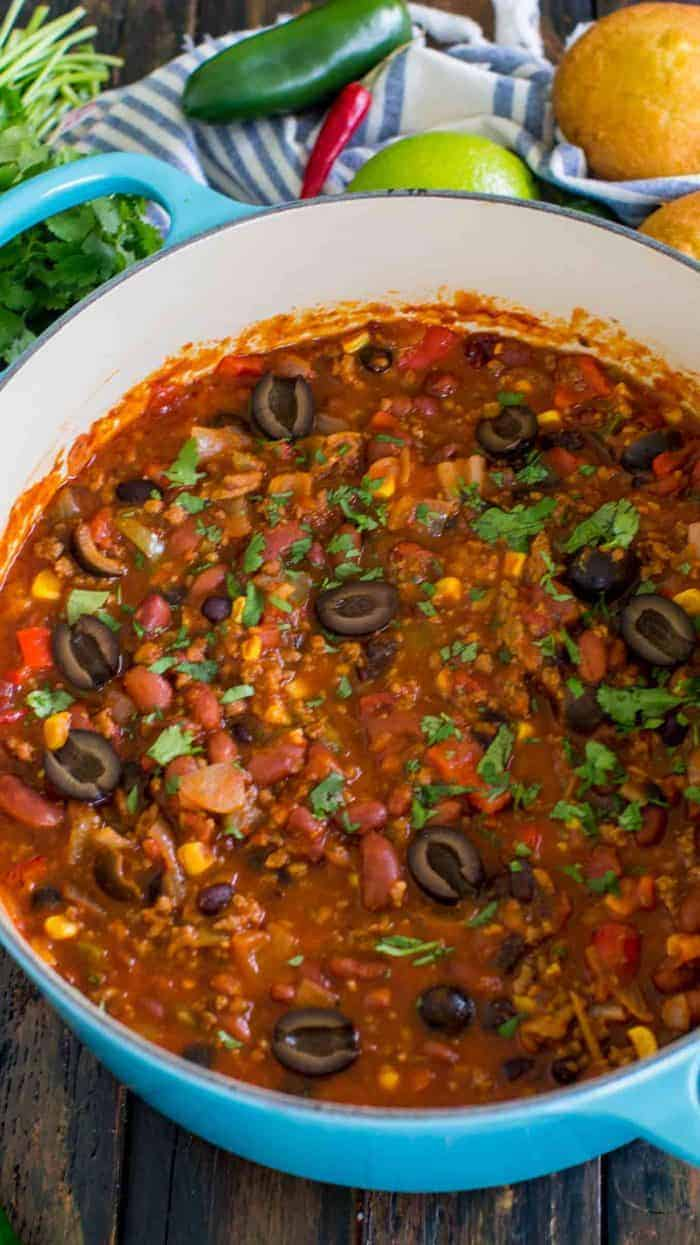 Taco Soup in a blue pot surrounded by veggies