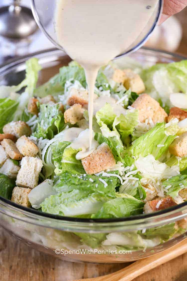 Caesar Salad Dressing being poured over romaine lettuce and croutons