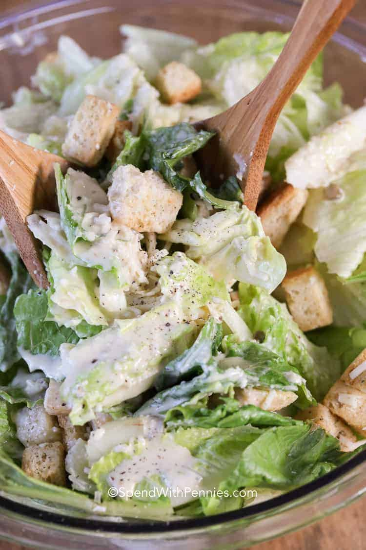 Caesar salad in a glass bowl with wooden utensils