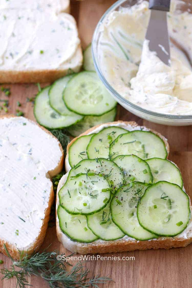 A slice of bread with sliced cucumbers and cream cheese spread
