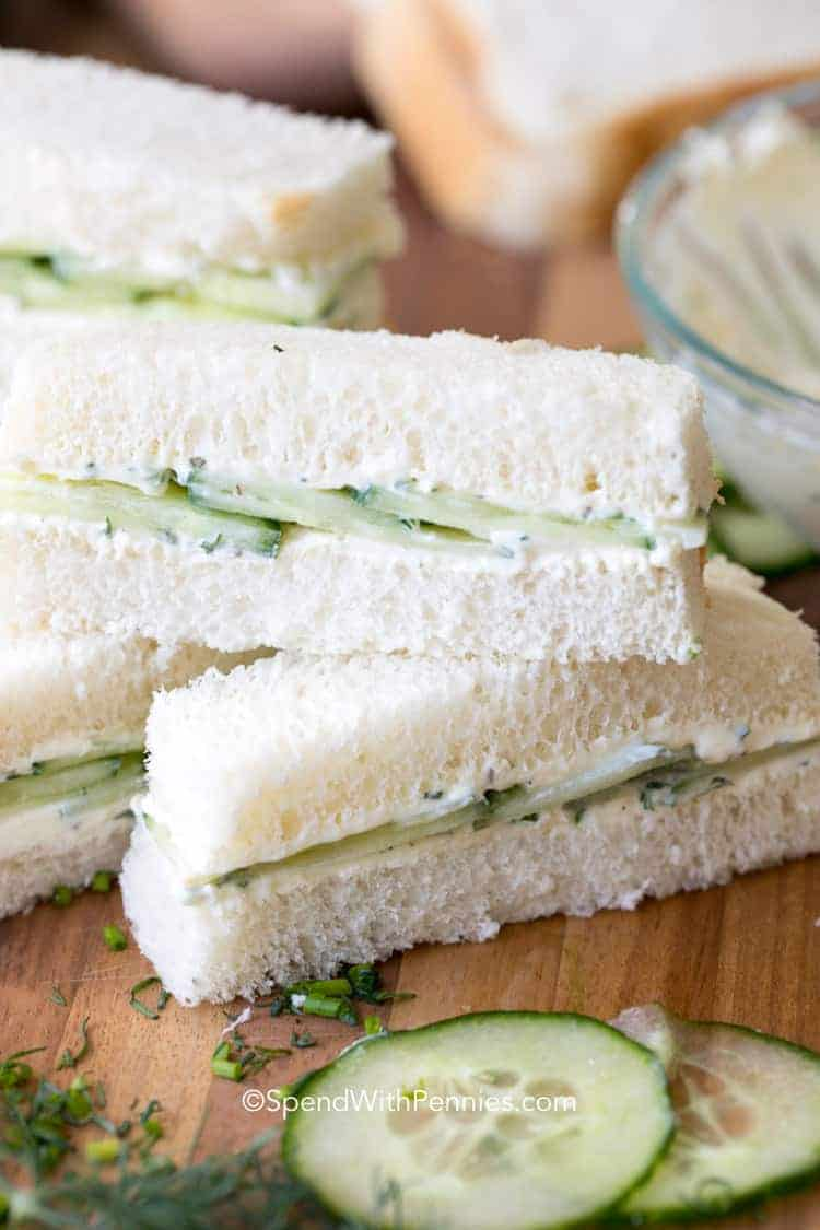 Cucumber Sandwiches cut into sticks and stacked on a cutting board.