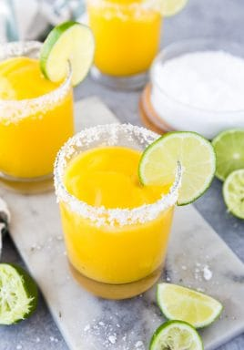A top down look at frozen mango margaritas in round glasses with salt rims and lime wedge with salt and lime on the side