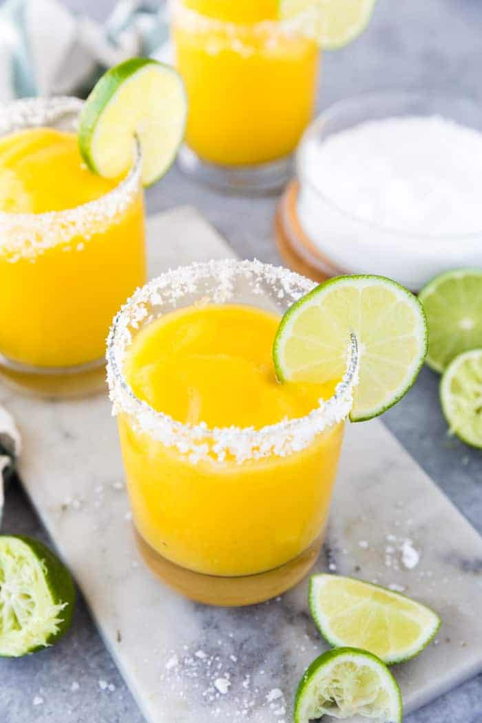 A top down look at frozen mango margaritas in round glasses with salt rims and lime wedge with salt and limes in the background