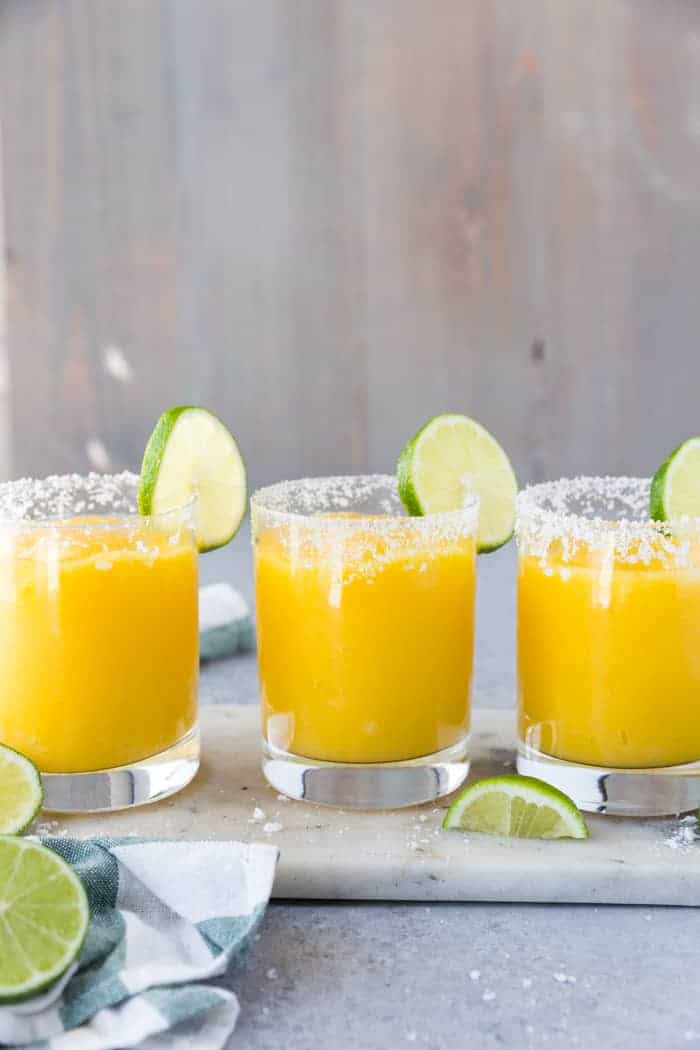 Three glasses lined up on a marble board with salt rims and lime wedges and filled with frozen mango margarita