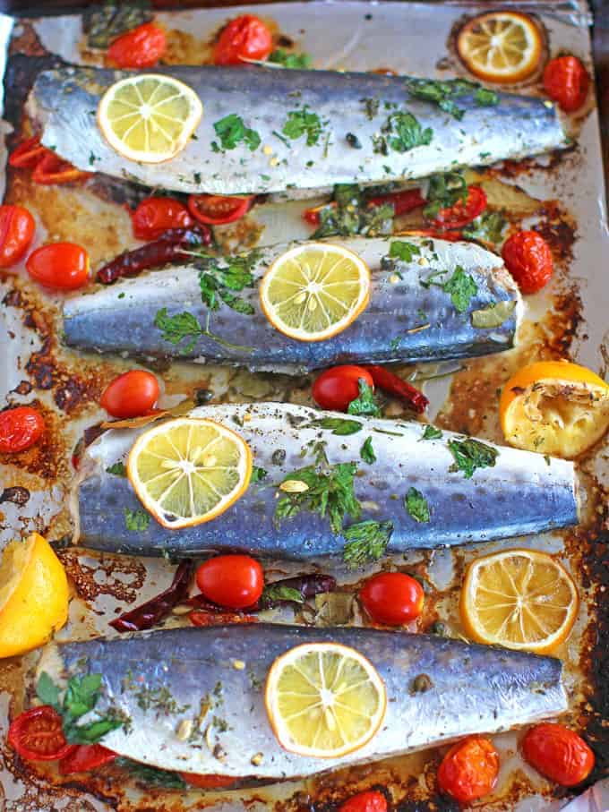 Oven Roasted Spanish Mackerel on a baking tray with lemons and tomatoes