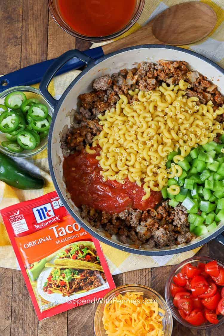 Uncooked Ingredients for taco pasta skillet in a pot including beef, raw macaroni and chopped bell peppers