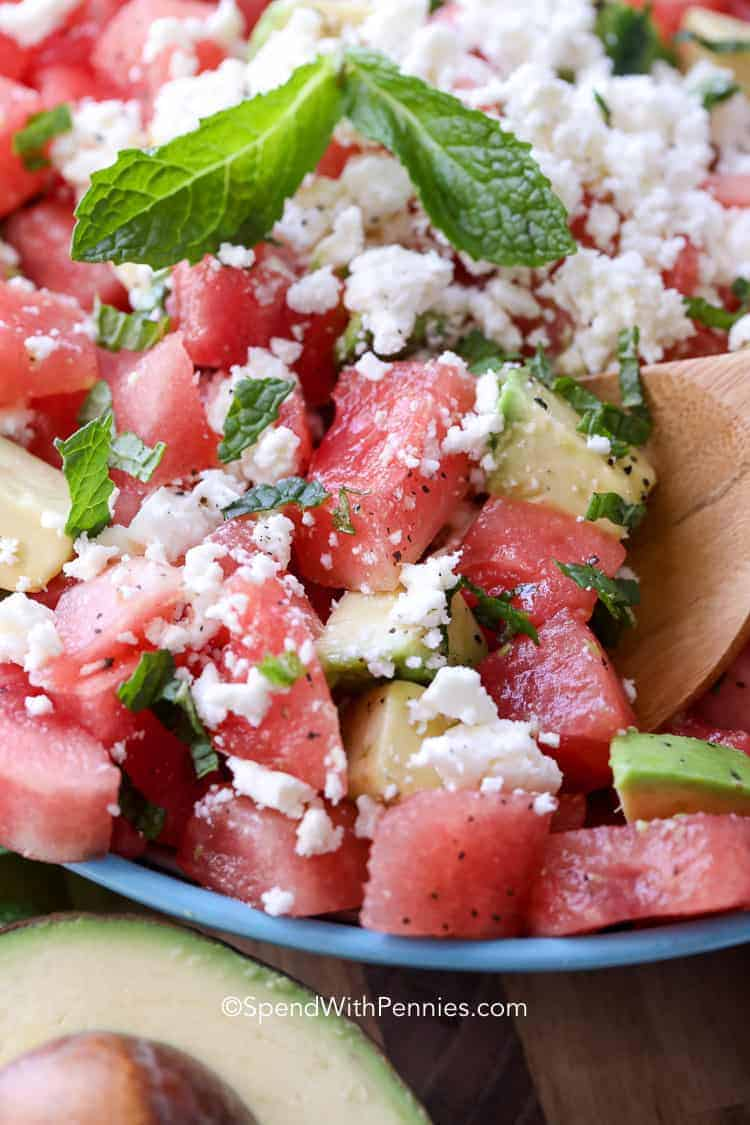 Close up of watermelon salad being scooped up with a spoon.