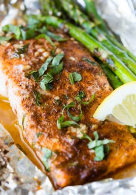 A fillet of salmon sitting on foil with a lemon wedge and asparagus