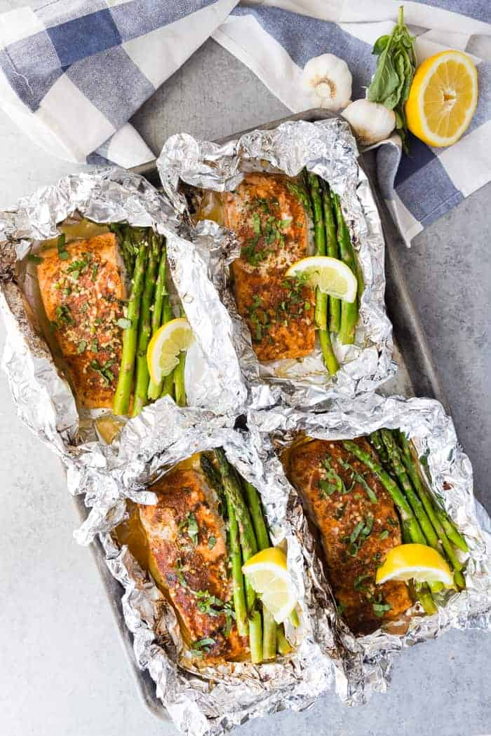 Four salmon fillets on a baking tray in foil with asparagus and lemon wedges with garlic and lemon in the background