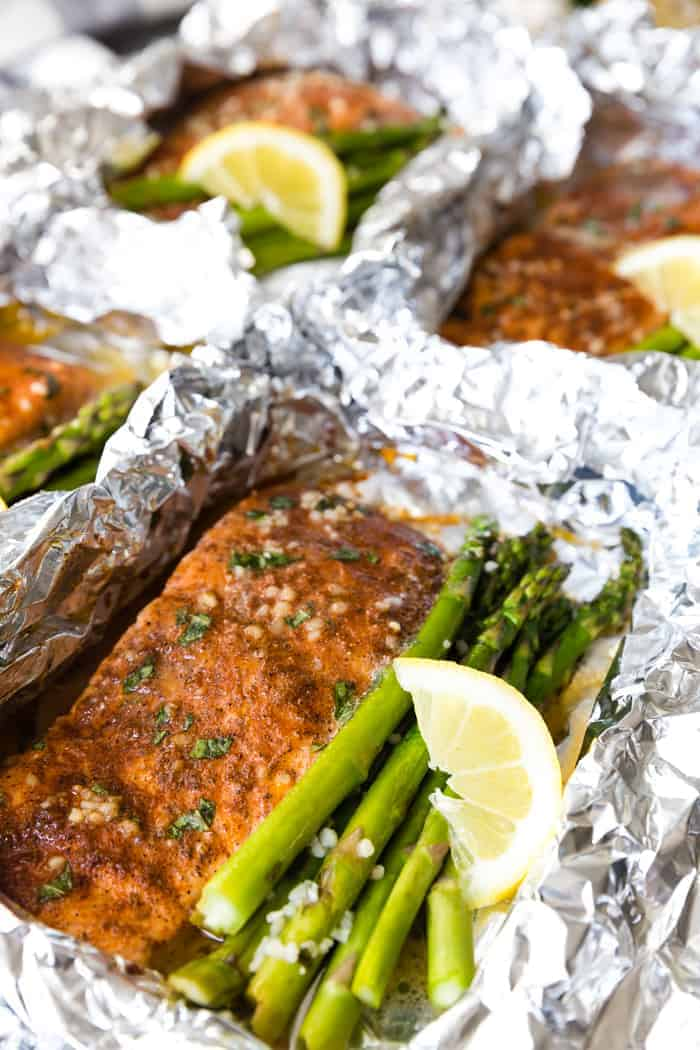 close up of a salmon fillet in a foil packet with asparagus spears and a lemon wedge