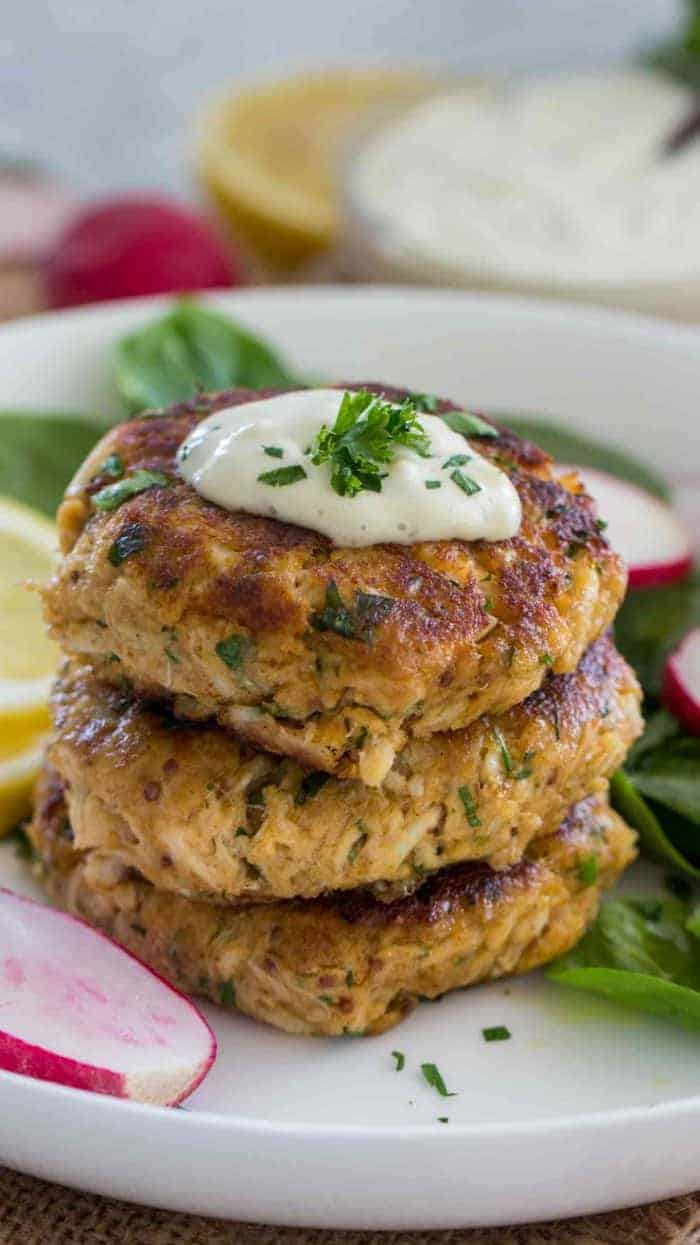 Three crab cakes in a stack with tartar sauce and garnish on a white plate