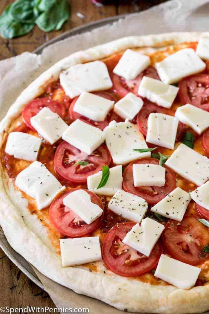 Margherita pizza before going into the oven with all ingredients including basil, tomatoes and mozzarella cheese