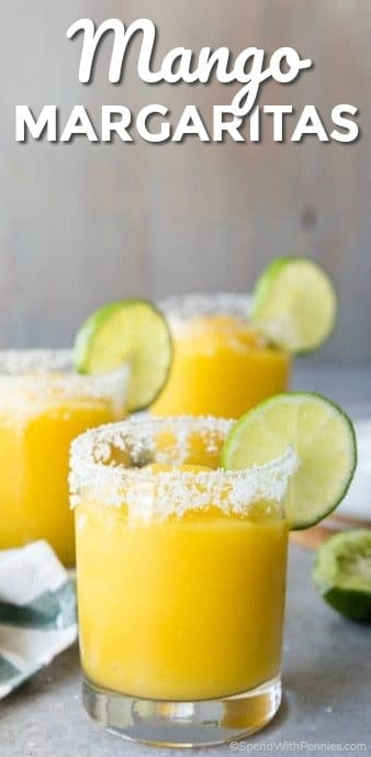 Mango Margaritas garnished with a slice of lime