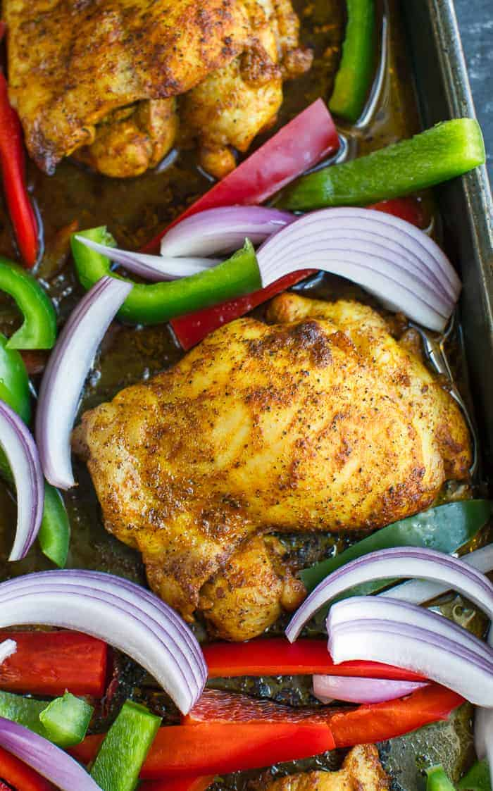 chicken shawarma with red onions and bell peppers on sheet pan close up
