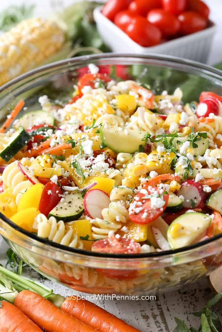 A serving bowl of pasta salad with summer vegetables, corn, carrots and tomatoes.