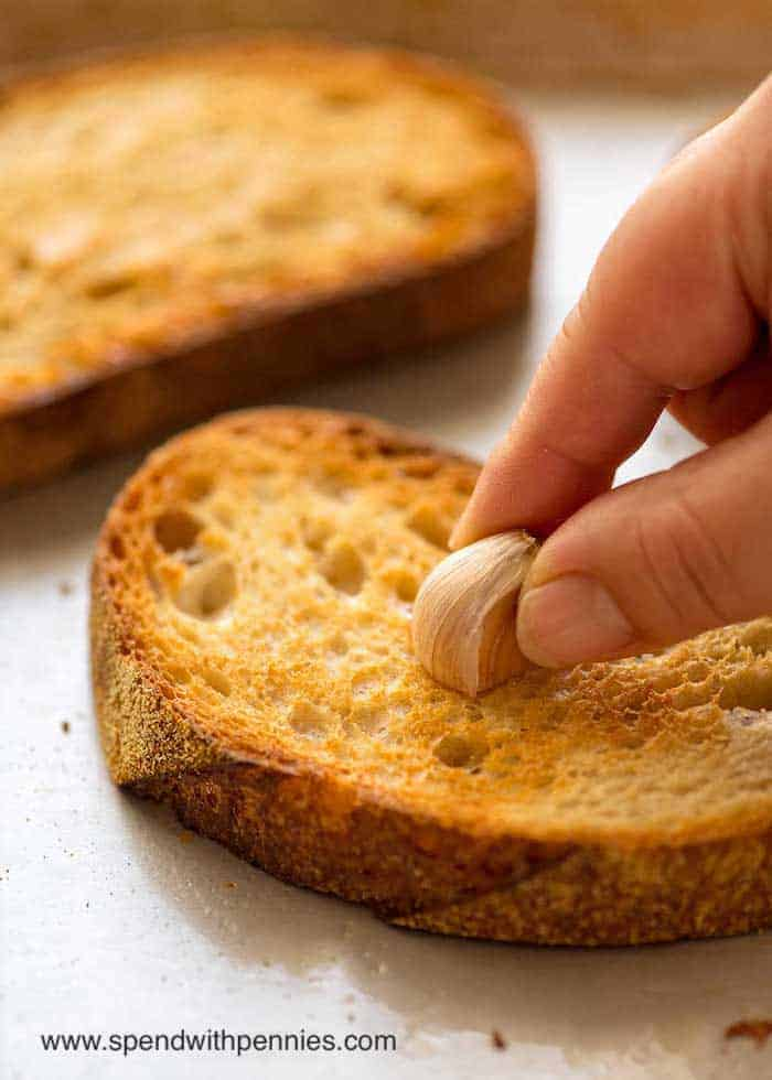 Garlic being spread on piece of toast