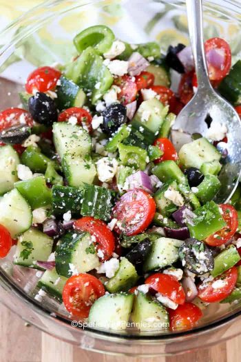 Greek Salad in a clear glass bowl with spoon