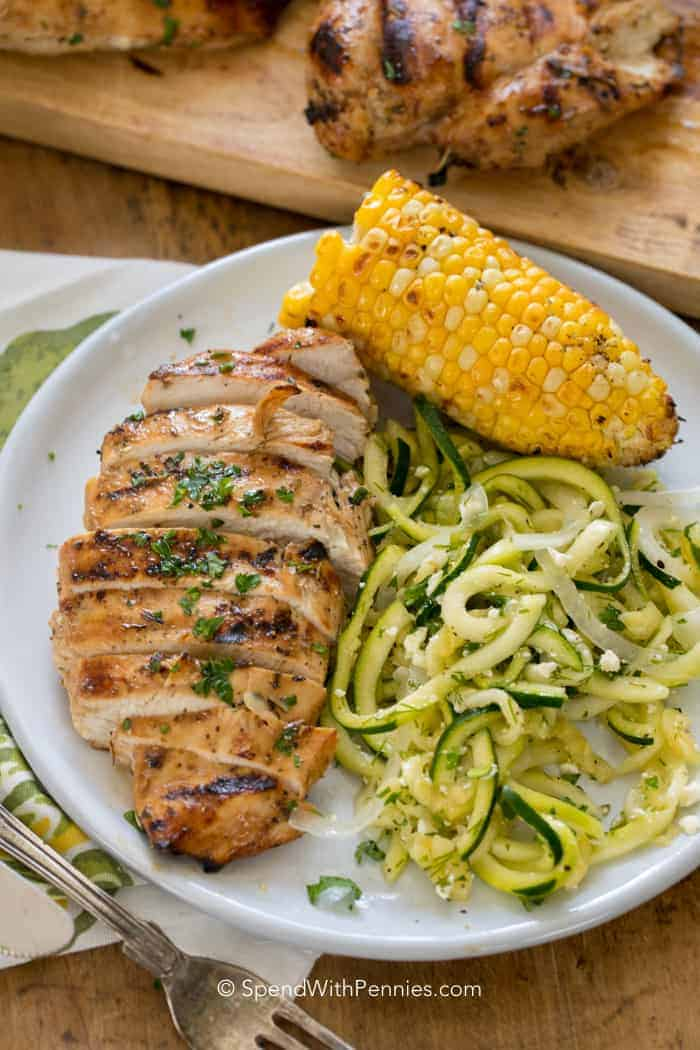 Easy Grilled Chicken Breast served as the main entree on a white plate with corn on the cob and spiralled zucchini
