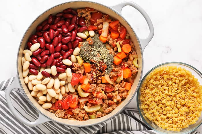 Ingredients like beans and carrots being added to fagioli soup.