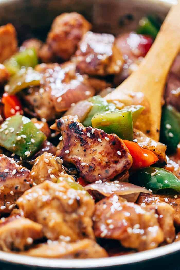 Close up of pepper chicken stir fry in a pan with a wooden spoon