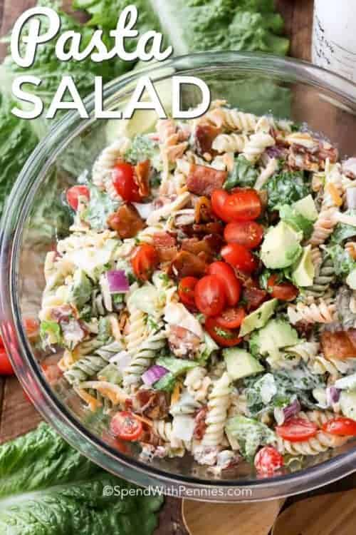 BLT Pasta Salad served in a clear bowl and garnished with tomatoes and bacon