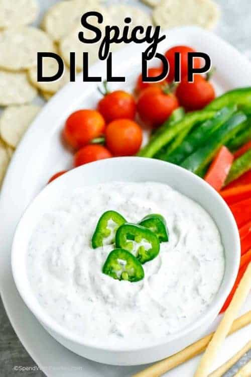 Spicy Dill Dip served in a white bowl with veggies on the side for dipping.