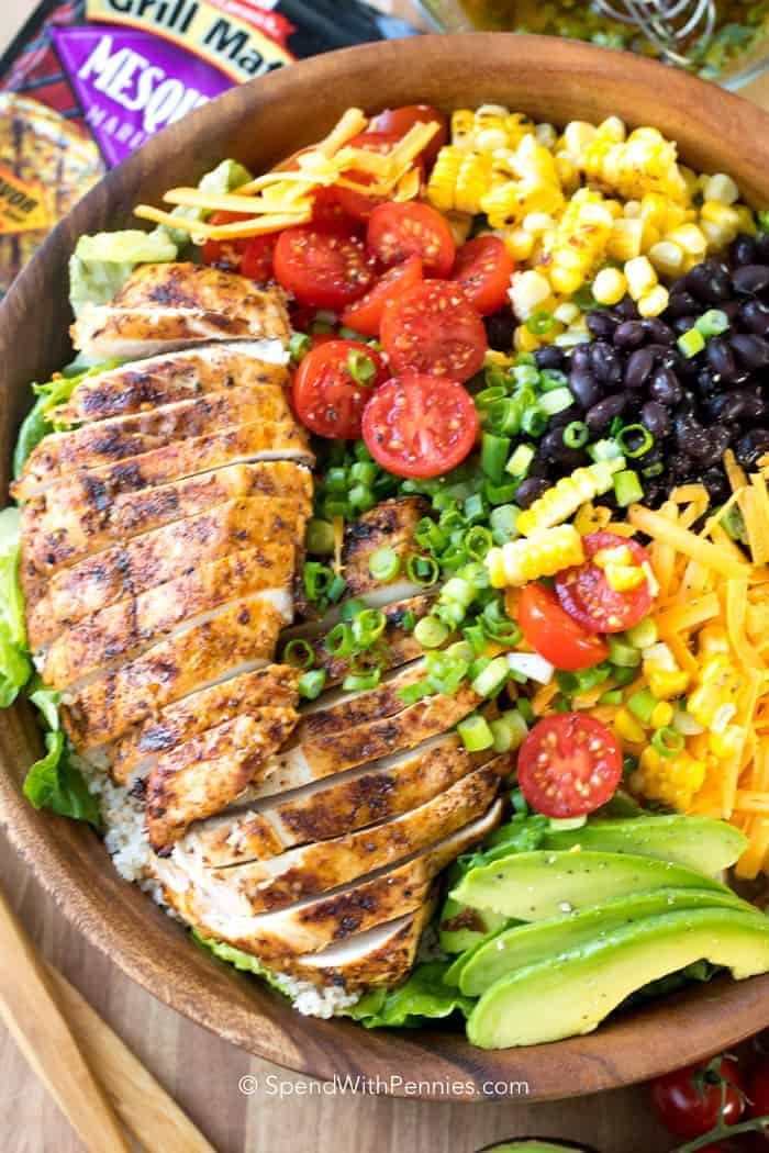 Southwest Salad with grilled chicken, tomatoes and veggies in a wood bowl.
