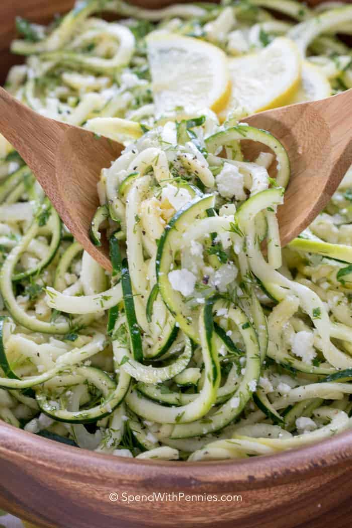 Serving Zucchini Salad with two wooden spoons