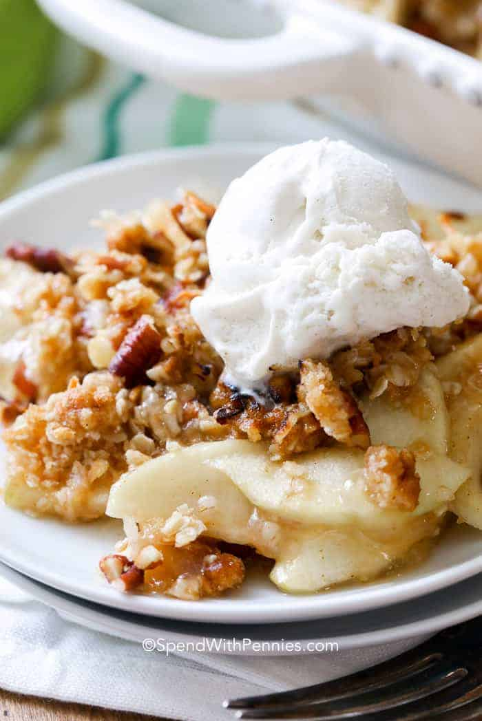 A serving of Apple Crisp topped with ice cream and served on a white plate