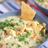 Slow cooker chicken pot pie soup in a grey bowl topped with herbs and pie crust