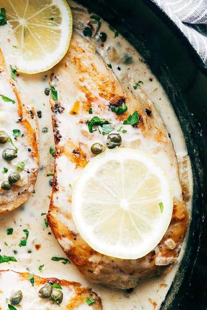 Closeup of creamy lemon chicken scallopini in a skillet with capers and lemon slices