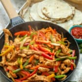 A pan of steaming chicken fajitas with tortillas