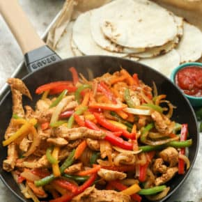 A pan of steaming chicken fajitas with tortillas on a pan with salsa and bell peppers