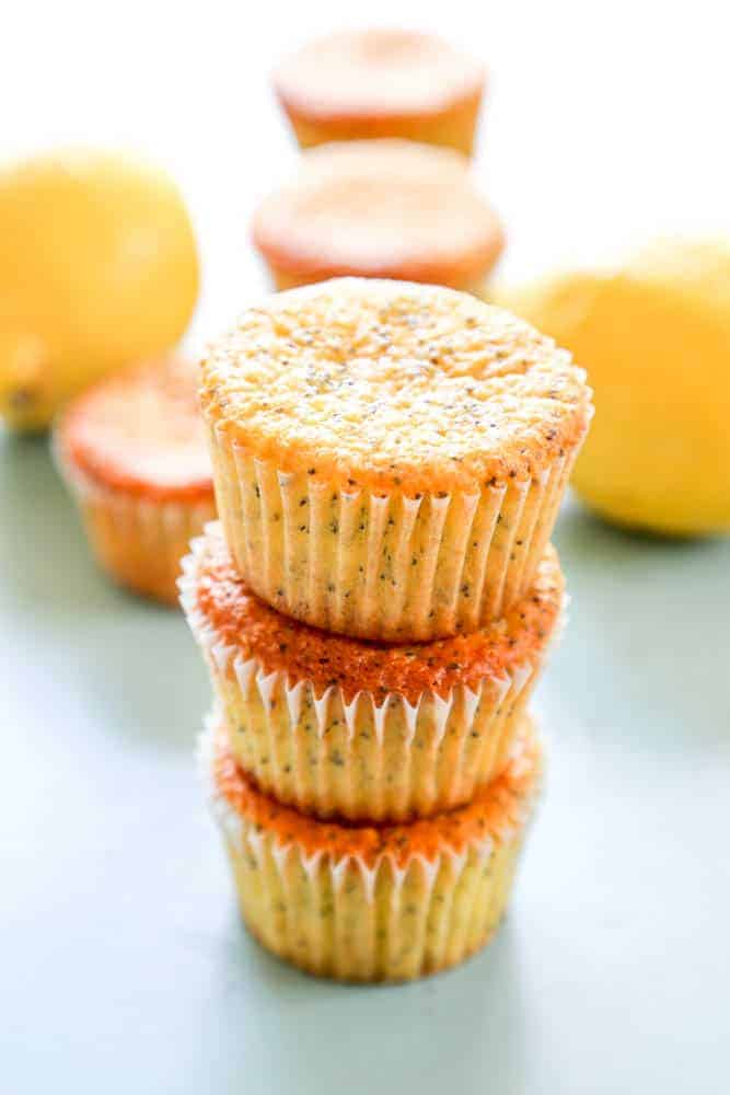 lemon poppy seed muffins piled in a stack with lemons in the background