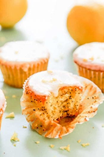 lemon poppy seed muffin with a bite out of it and a couple of muffins in the background
