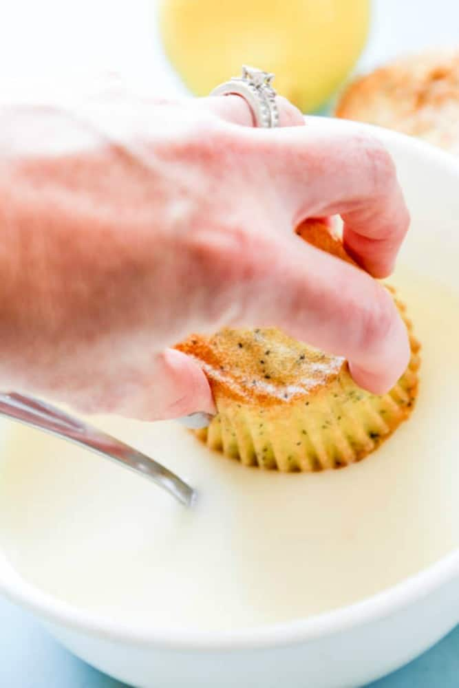 hand dipping a lemon poppy seed muffin in glaze in a white bowl