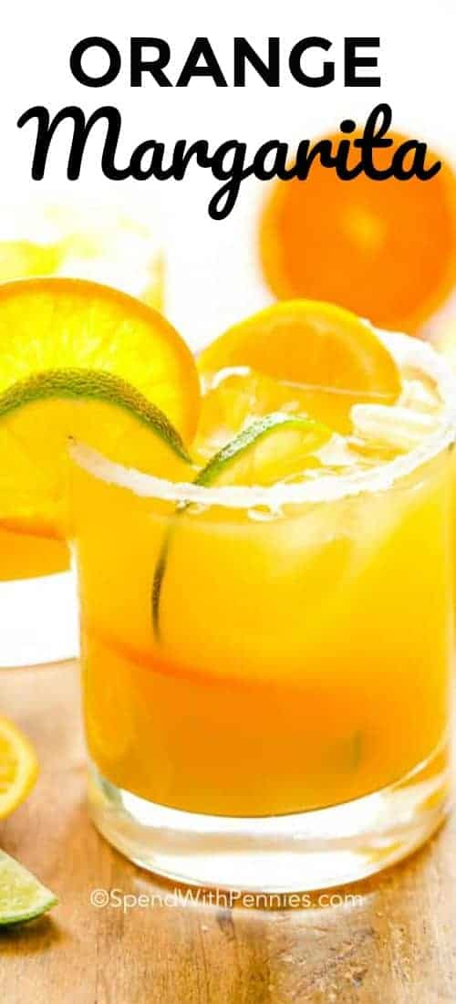 A glass of Orange Margarita garnished with orange and lime slices