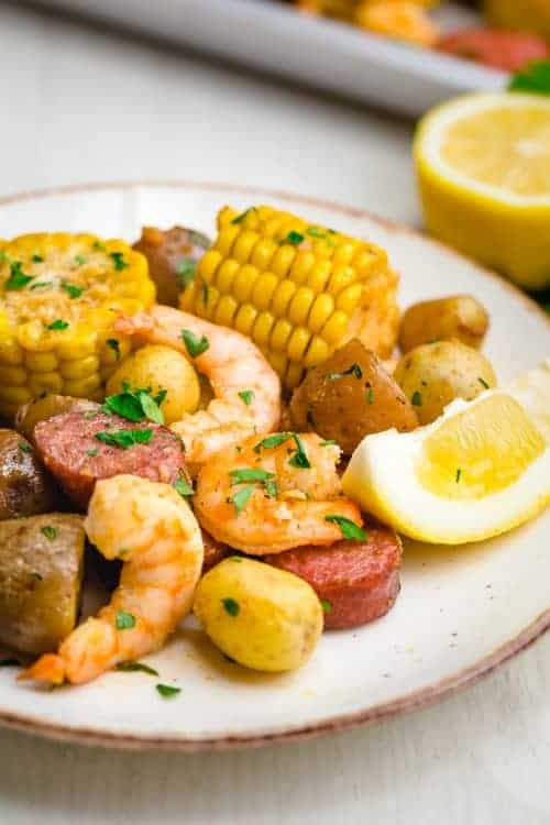 white plate with shrimp, sausage. lemon wedge, corn, on it garnished with parsley