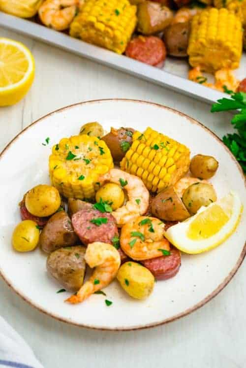 Sheet pan shrimp boil, a white plate of shrimp boil with a sheet pan to the side.