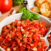 Bruschetta in a white bowl and a spoon with ingredients in the background