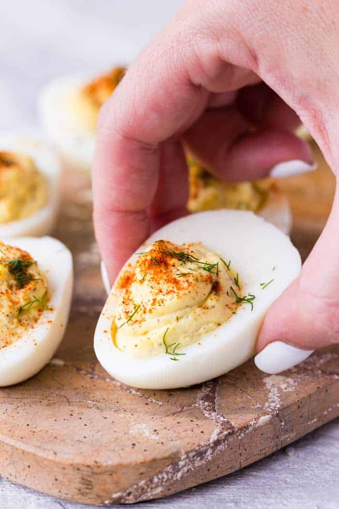Classic Deviled Egg on a brown cutting board being picked up