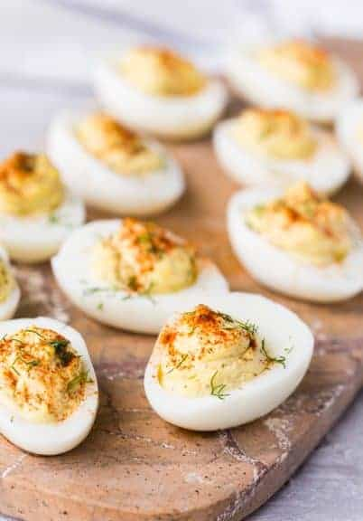 Brown cutting board topped with a dozen classic deviled eggs with paprika and dill garnish