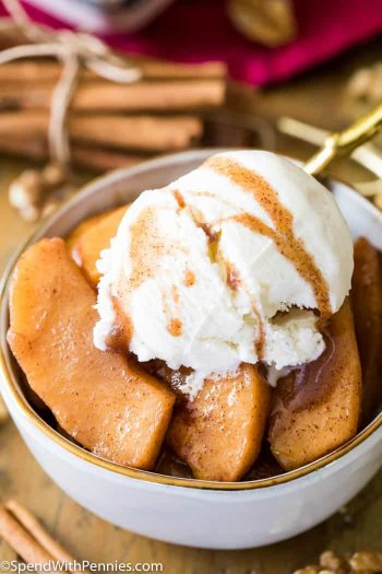 baked apples in a white bowl topped with ice cream